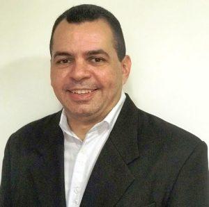 Foto do palestrante: um homem branco, de cabelo curto e escuro, usando um blazer preto e uma camisa social branca e sorrindo para a câmera