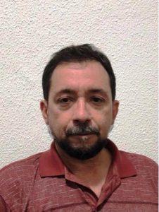 Foto do palestrante: um homem branco, de bigode e barba, usando uma camisa vermelha de gola polo