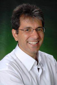 Foto do palestrante: um homem branco, de cabelo grisalho e óculos, sorrindo para a câmera