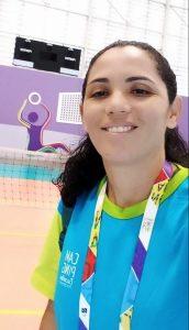 Foto da palestrante: uma mulher branca, de cabelo ondulado e escuro, com uma camisa e um crachá coloridos com temática esportiva. Ela sorri para a câmera.