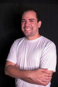 Foto do palestrante: um homem branco, de camisa branca e braços cruzados, sorrindo para a câmera