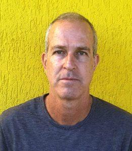 Foto do palestrante: um homem branco, de cabelo curto e grisalho, em frente a uma parede amarela