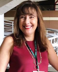 Foto da palestrante: uma mulher branca, sorrindo para a câmera. Ela usa batom vermelho, colares, um crachá e uma blusa vinho