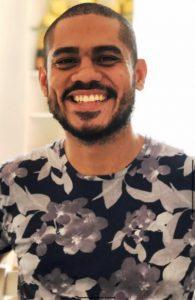 Foto do palestrante: um homem negro, de barba, bigode e cabelo curtos, sorrindo para a câmera. Ele usa uma camisa floral preta e cinza.