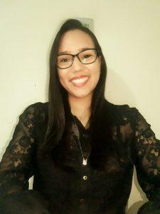 Foto da palestrante: uma mulher jovem de óculos e camisa preta de mangas, sorrindo para a câmera
