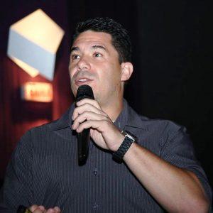 Foto do palestrante: um homem com uma camisa escura e relógio segurando um microfone