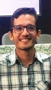 Foto do palestrante: um homem jovem, de óculos e camisa xadrez
