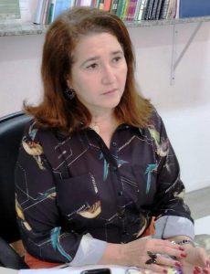 Foto da palestrante: uma mulher branca e ruiva, de camisa social estampada