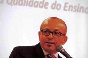 Foto do palestrante: um homem careca, de óculos e cavanhaque falando em um microfone