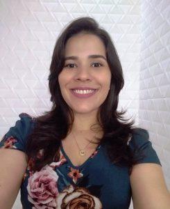 Foto da palestrante: uma mulher sorrindo para a câmera. Ela tem cabelos pretos ondulados e usa uma blusa estampada