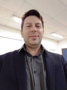 Foto do palestrante: um homem branco, de cabelo curto e preto, usando camisa social e blazer escuros