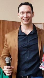 Foto do palestrante: um homem branco, de camisa social escura e blazer caramelo, segurando um microfone e sorrindo para a câmera